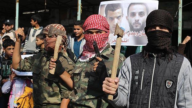 Enmascarados celebran en Rafah (Gaza) la muerte de cuatro israelíes en una sinagoga de Jerusalén. Foto: REUTERS/Ibraheem Abu Mustafa