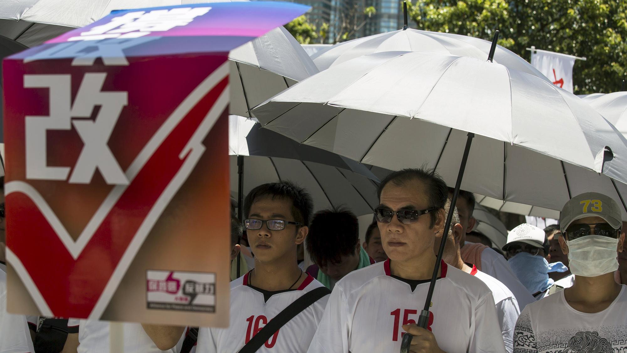 """Manifestantes prochinos con una pancarta en la que se lee """"Apoyad el sufragio universal"""", ante el Consejo Legislativo (Asamblea) de Hong Kong. REUTERS/Tyrone Siu"""